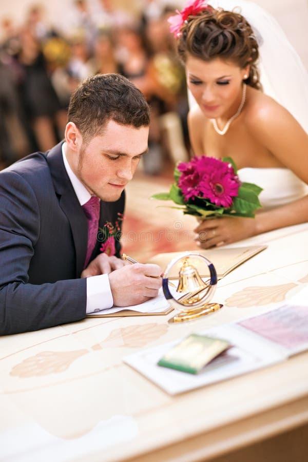 Νέο ζεύγος που υπογράφει τα γαμήλια έγγραφα στοκ φωτογραφία