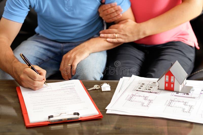 Νέο ζεύγος που υπογράφει τη σύμβαση δανείου για ένα σπίτι στοκ φωτογραφία