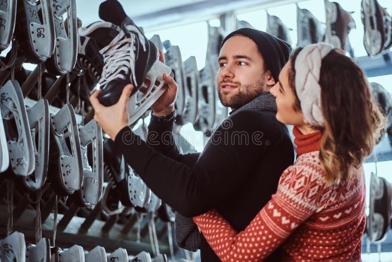 Νέο ζεύγος που φορά τα θερμά ενδύματα που στέκονται κοντά στο ράφι με πολλά ζευγάρια των σαλαχιών, που επιλέγουν το μέγεθός του στοκ εικόνα με δικαίωμα ελεύθερης χρήσης