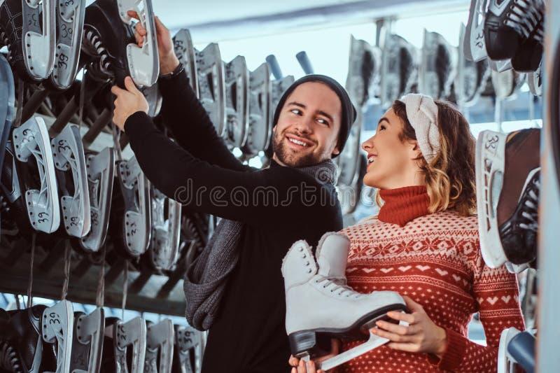 Νέο ζεύγος που φορά τα θερμά ενδύματα που στέκονται κοντά στο ράφι με πολλά ζευγάρια των σαλαχιών, που επιλέγουν το μέγεθός του στοκ εικόνες