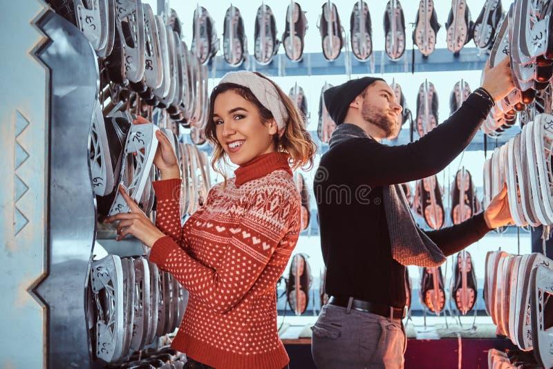 Νέο ζεύγος που φορά τα θερμά ενδύματα που στέκονται κοντά στο ράφι με πολλά ζευγάρια των σαλαχιών, που επιλέγουν το μέγεθός του στοκ φωτογραφία με δικαίωμα ελεύθερης χρήσης