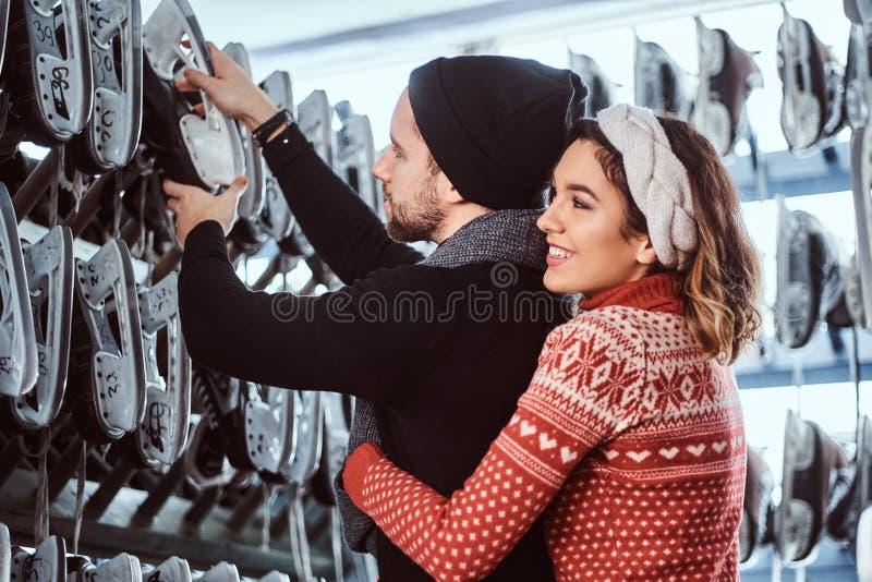 Νέο ζεύγος που φορά τα θερμά ενδύματα που στέκονται μαζί, που επιλέγουν τα ζευγάρια των σαλαχιών κοντά στο ράφι μέσα στοκ φωτογραφία με δικαίωμα ελεύθερης χρήσης