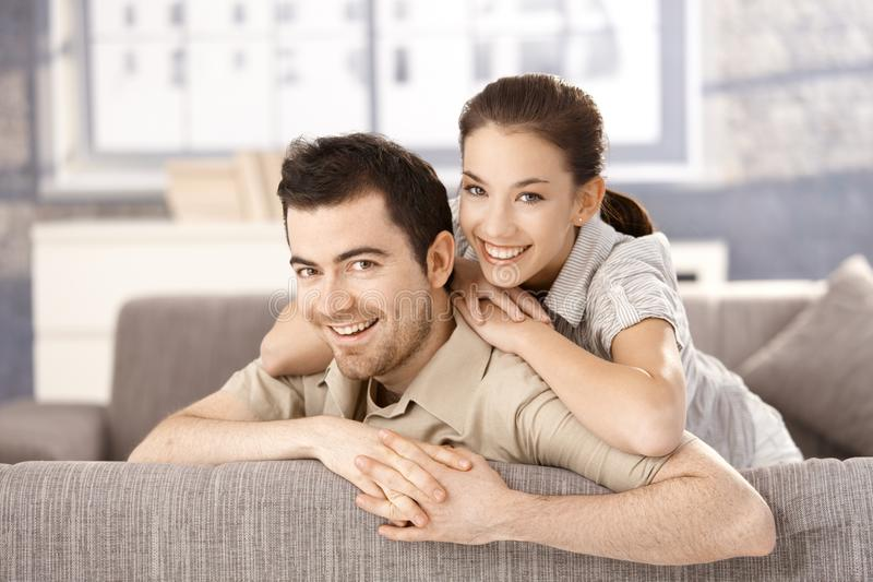Νέο ζεύγος που χαμογελά ευτυχώς στον καναπέ στο σπίτι στοκ φωτογραφία με δικαίωμα ελεύθερης χρήσης