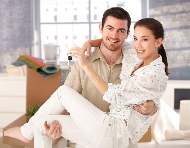 Νέο ζεύγος που χαμογελά ευτυχώς στο καινούργιο σπίτι στοκ φωτογραφία