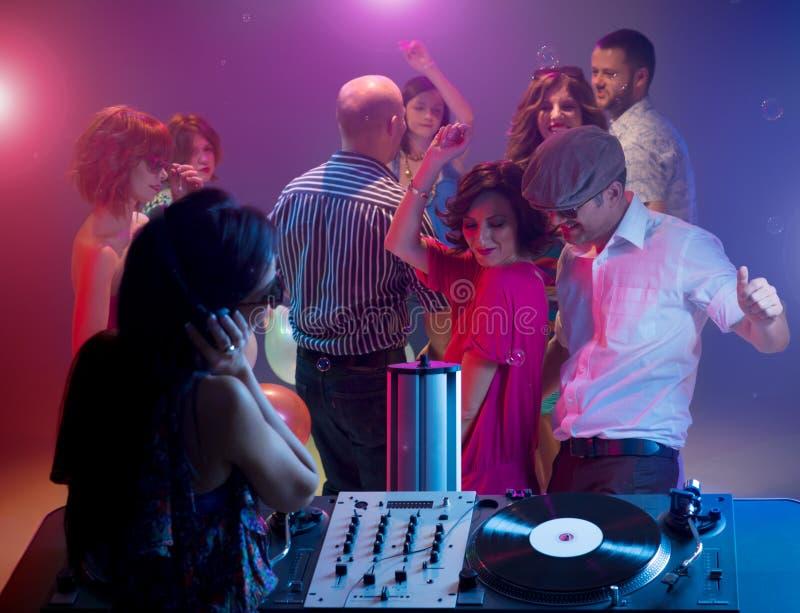 Νέο ζεύγος που χορεύει στο συμβαλλόμενο μέρος με το θηλυκό DJ στοκ φωτογραφίες