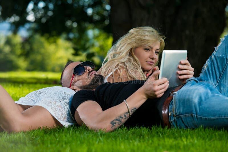 Νέο ζεύγος που χρησιμοποιεί μια ψηφιακή ταμπλέτα στο πάρκο στοκ εικόνα με δικαίωμα ελεύθερης χρήσης