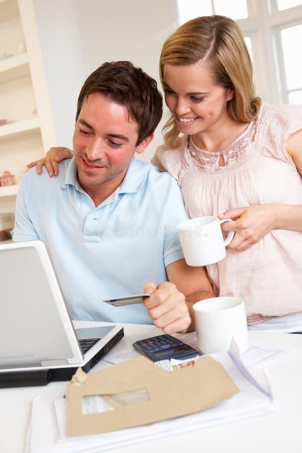 Νέο ζεύγος που χρησιμοποιεί την πιστωτική κάρτα στο διαδίκτυο στοκ φωτογραφία με δικαίωμα ελεύθερης χρήσης