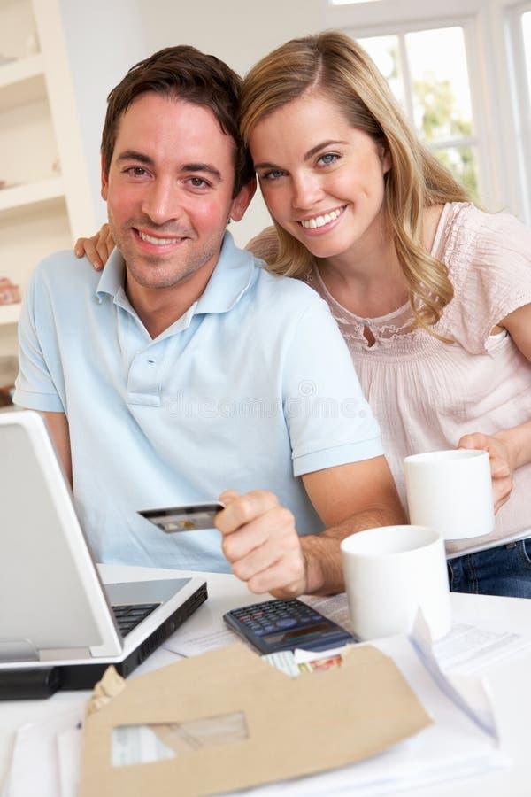 Νέο ζεύγος που χρησιμοποιεί την πιστωτική κάρτα στο διαδίκτυο στοκ φωτογραφία