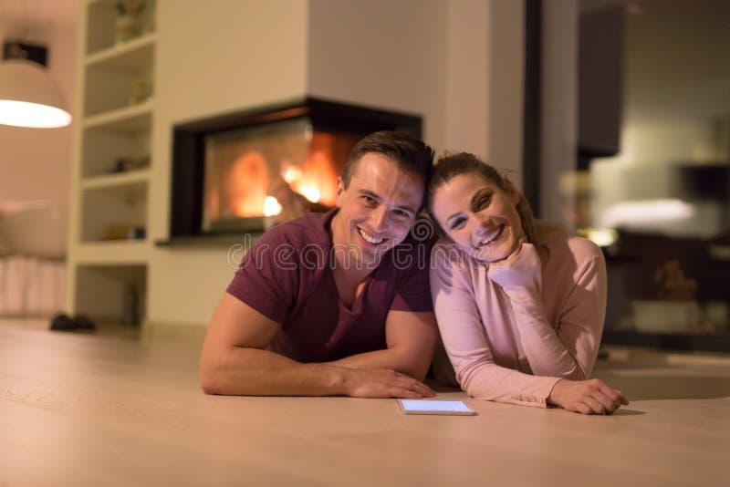 Νέο ζεύγος που χρησιμοποιεί την ψηφιακή ταμπλέτα στην κρύα χειμερινή νύχτα στοκ φωτογραφία