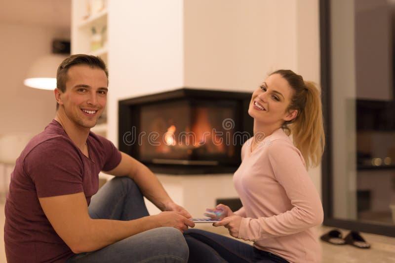 Νέο ζεύγος που χρησιμοποιεί την ψηφιακή ταμπλέτα στην κρύα χειμερινή νύχτα στοκ εικόνα