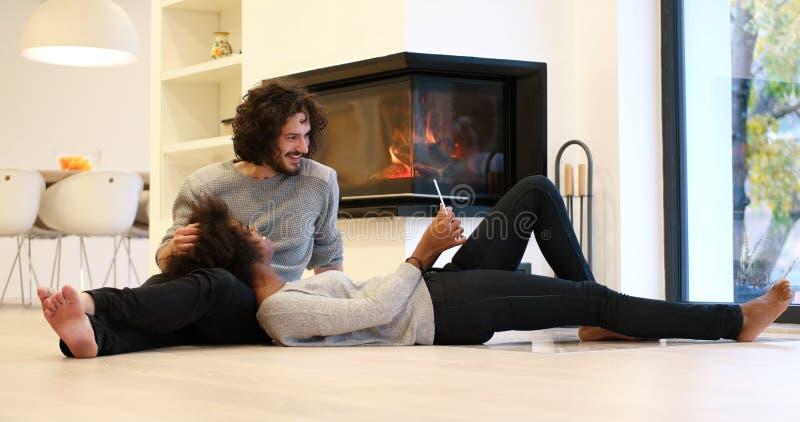 Νέο ζεύγος που χρησιμοποιεί την ψηφιακή ταμπλέτα στο πάτωμα στοκ φωτογραφίες με δικαίωμα ελεύθερης χρήσης