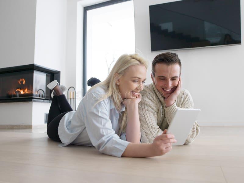 Νέο ζεύγος που χρησιμοποιεί το κινητό τηλέφωνο στο πάτωμα στοκ φωτογραφία