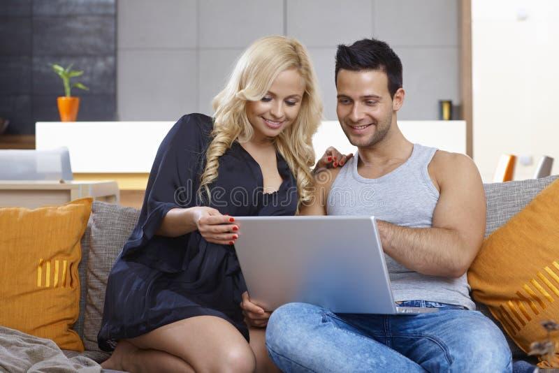 Νέο ζεύγος που χρησιμοποιεί το φορητό προσωπικό υπολογιστή στο σπίτι στοκ εικόνα