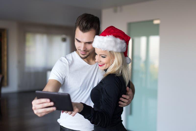 Νέο ζεύγος που ψωνίζει on-line για τα Χριστούγεννα από την ταμπλέτα στο σπίτι στοκ φωτογραφία με δικαίωμα ελεύθερης χρήσης