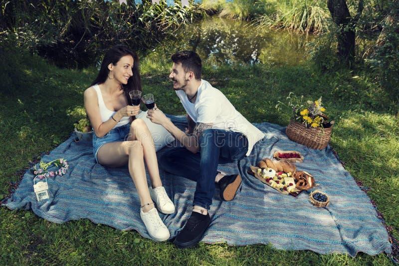 Νέο ζεύγος σε ένα πικ-νίκ σε μια συνεδρίαση πάρκων πόλεων σε ένα κάλυμμα και ένα κόκκινο κρασί κατανάλωσης στοκ φωτογραφίες
