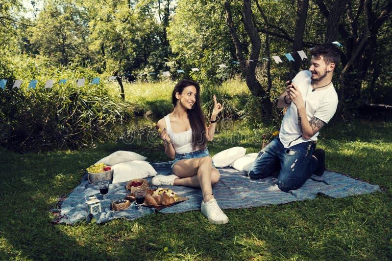 Νέο ζεύγος σε ένα πικ-νίκ σε μια συνεδρίαση πάρκων πόλεων σε ένα κάλυμμα παίρνει μια εικόνα της στοκ φωτογραφία