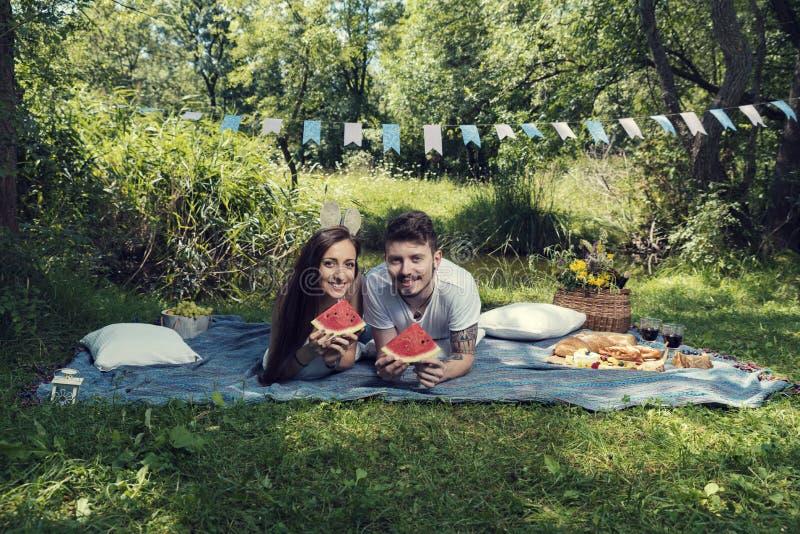 Νέο ζεύγος σε ένα πικ-νίκ που καθορίζει σε ένα κάλυμμα και που τρώει το καρπούζι στοκ εικόνα
