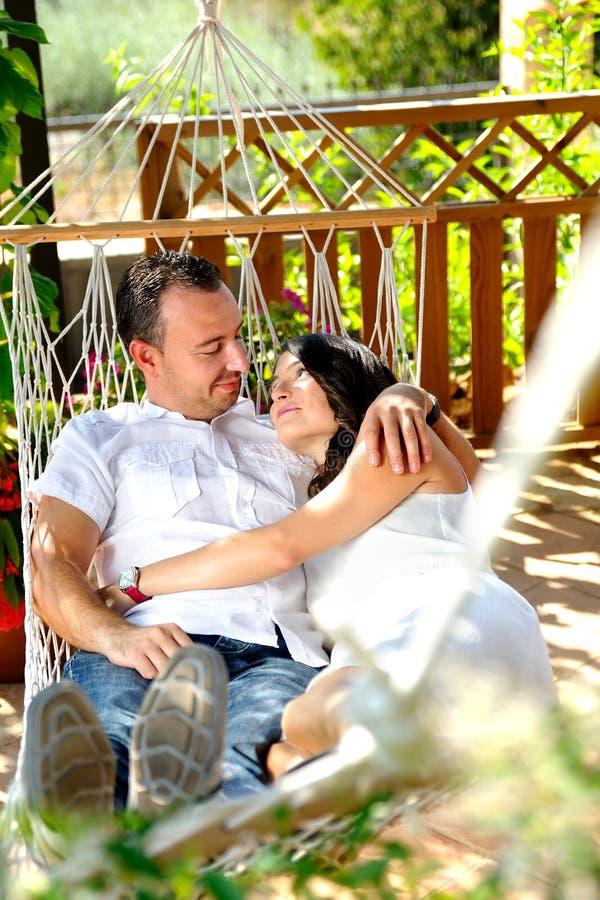 Νέο ζεύγος σε μια αιώρα σχοινιών σε ένα εξοχικό σπίτι οπισθοσκόπο στοκ εικόνες