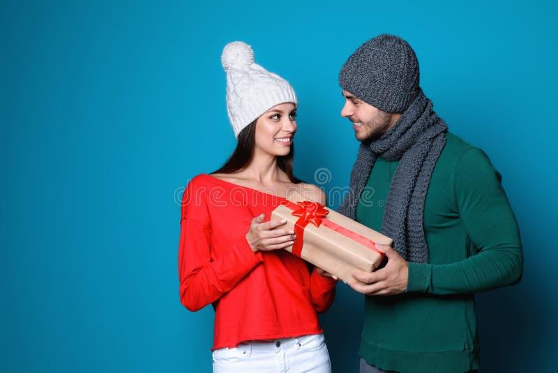 Νέο ζεύγος στα θερμά ενδύματα με το δώρο Χριστουγέννων στοκ εικόνες με δικαίωμα ελεύθερης χρήσης