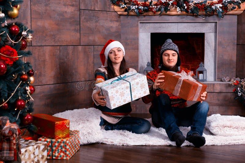 Νέο ζεύγος στα θερμά πουλόβερ και το αστείο δόσιμο χειμερινών καπέλων prese στοκ φωτογραφία με δικαίωμα ελεύθερης χρήσης