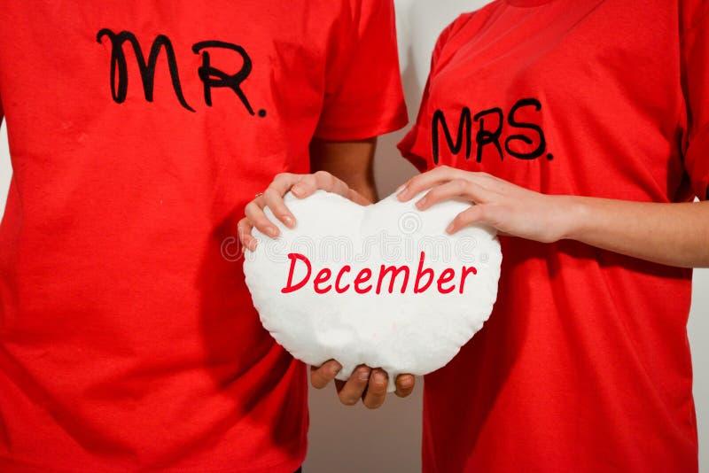 Νέο ζεύγος στα κόκκινα πουκάμισα που κρατά την άσπρη καρδιά υφάσματος με το κείμενο στοκ φωτογραφίες