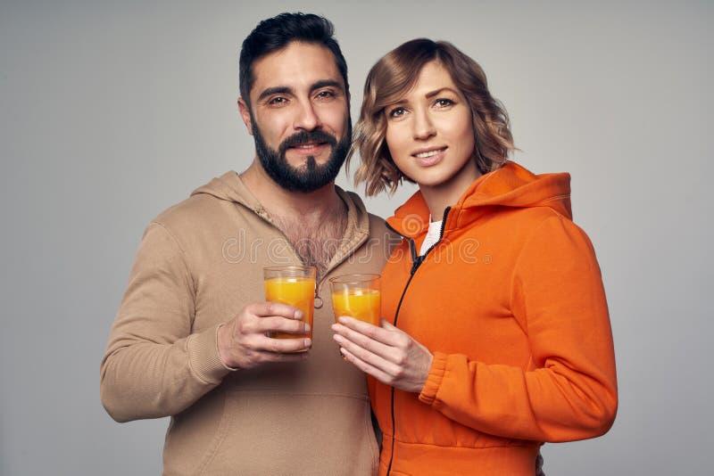 Νέο ζεύγος στα περιστασιακά ποτήρια εκμετάλλευσης του χυμού από πορτοκάλι στοκ εικόνες με δικαίωμα ελεύθερης χρήσης