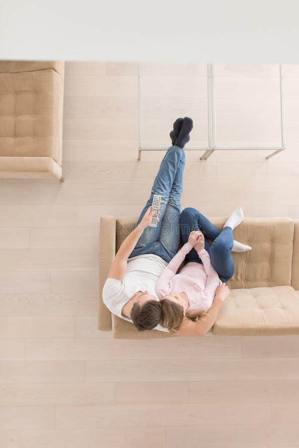 Νέο ζεύγος στην τηλεοπτική τοπ άποψη προσοχής καναπέδων στοκ φωτογραφία
