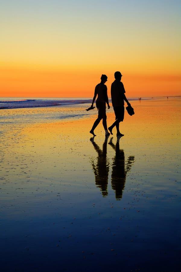Νέο ζεύγος στη ρομαντική παραλία στο ηλιοβασίλεμα στοκ εικόνες