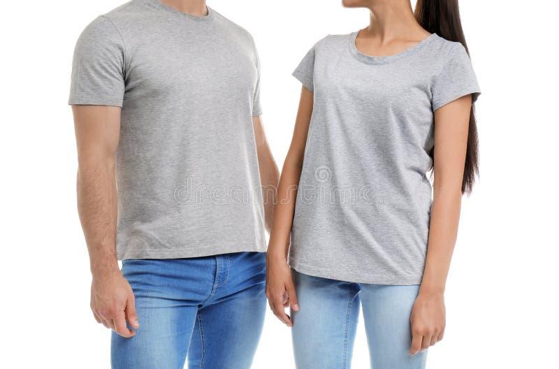 Νέο ζεύγος στις μπλούζες στο άσπρο υπόβαθρο στοκ φωτογραφίες