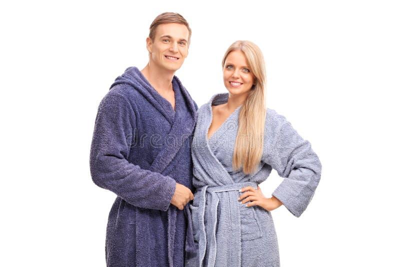 Νέο ζεύγος στο μπλε αγκάλιασμα μπουρνουζιών στοκ φωτογραφία με δικαίωμα ελεύθερης χρήσης