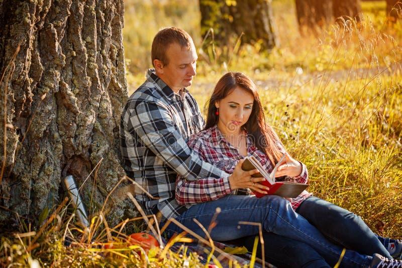 Νέο ζεύγος στο ξύλο φθινοπώρου στο βιβλίο πικ-νίκ και ανάγνωσης στοκ εικόνες