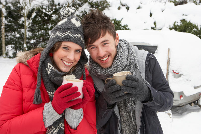 Νέο ζεύγος στο χιόνι με το αυτοκίνητο στοκ εικόνα