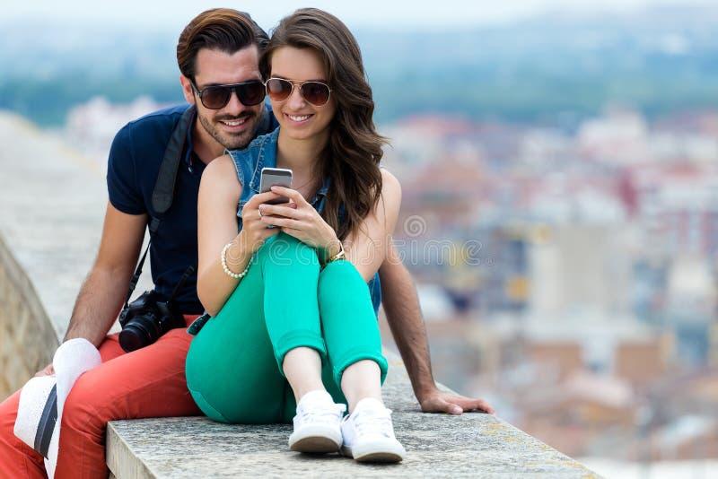 Νέο ζεύγος του τουρίστα στην πόλη που χρησιμοποιεί το κινητό τηλέφωνο στοκ φωτογραφία με δικαίωμα ελεύθερης χρήσης