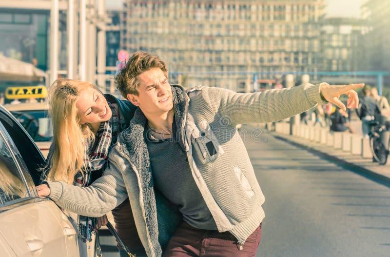Νέο ζεύγος των εραστών που εξετάζουν ένα αμάξι ταξί στην πόλη του Βερολίνου στοκ φωτογραφίες με δικαίωμα ελεύθερης χρήσης