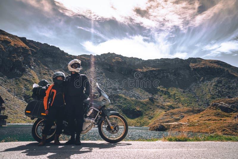 Νέο ζεύγος των ταξιδιωτών μοτοσικλετών στα βουνά φθινοπώρου της Ρουμανίας Ταξιδιωτικός τρόπος ζωής τουρισμού Moto και moto ενώ στοκ φωτογραφίες με δικαίωμα ελεύθερης χρήσης