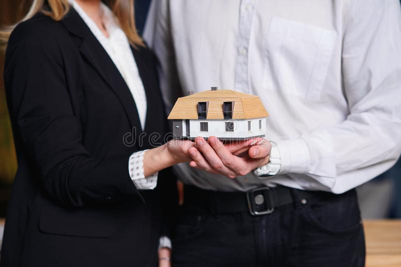 Νέο ζεύγος, realtor που κρατά το τρισδιάστατο πρότυπο του σπιτιού στοκ φωτογραφία