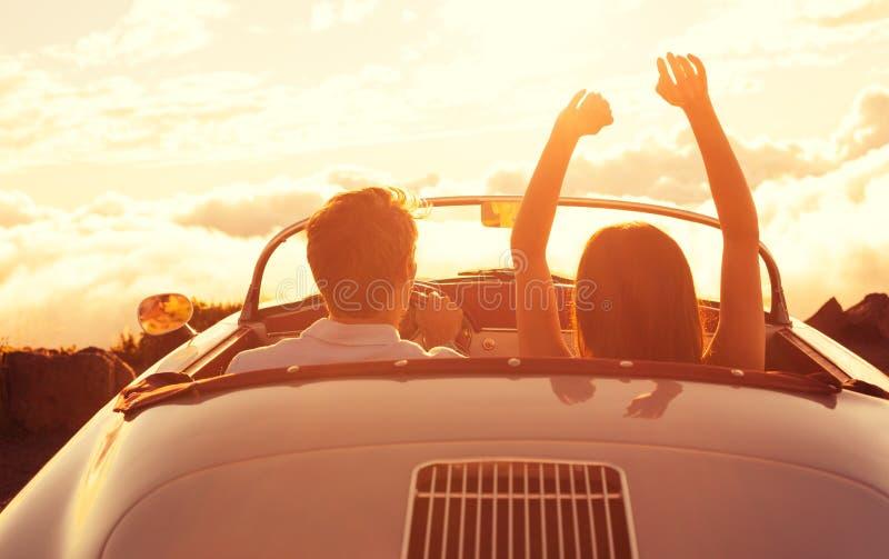 Νέο ζεύγος Wathcing το ηλιοβασίλεμα στο εκλεκτής ποιότητας αθλητικό αυτοκίνητο στοκ εικόνα με δικαίωμα ελεύθερης χρήσης