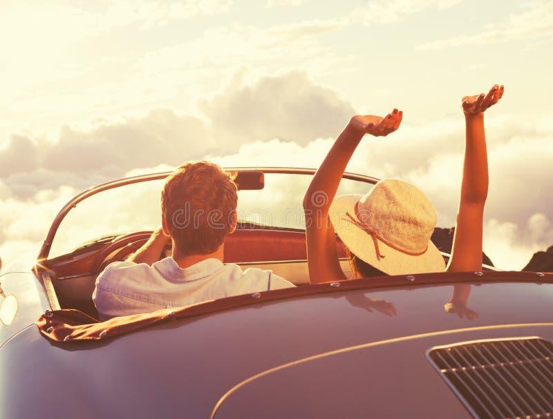 Νέο ζεύγος Wathcing το ηλιοβασίλεμα στο εκλεκτής ποιότητας αθλητικό αυτοκίνητο στοκ φωτογραφία με δικαίωμα ελεύθερης χρήσης