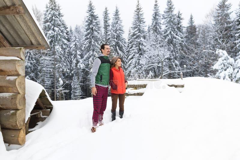 Νέο ζεύγους χιονώδες χειμερινού χιονιού ανδρών και γυναικών του χωριού ξύλινο εξοχικών σπιτιών εξοχικό σπίτι θερέτρου στοκ εικόνες με δικαίωμα ελεύθερης χρήσης