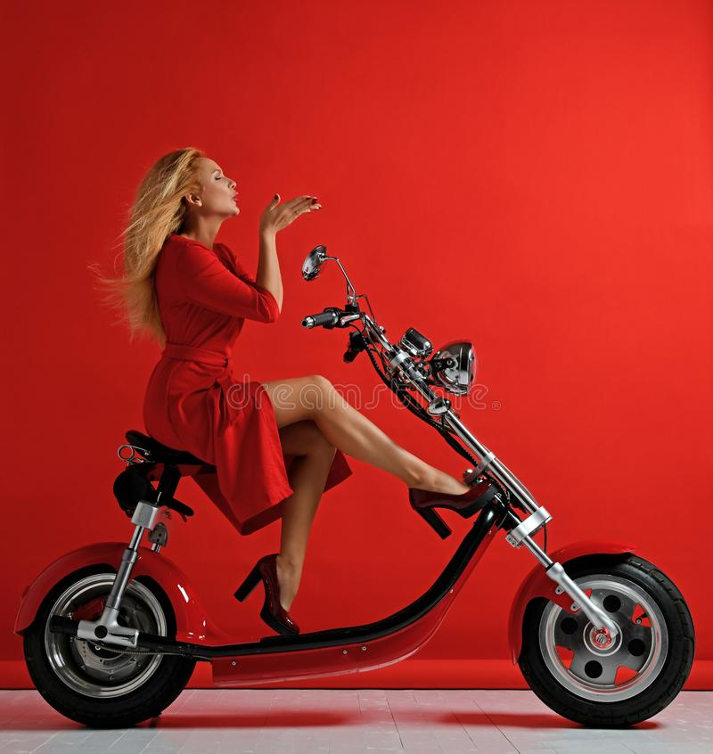 Νέο ηλεκτρικό μηχανικό δίκυκλο ποδηλάτων μοτοσικλετών αυτοκινήτων γύρου γυναικών παρόν για το νέο έτος 2019 στο κόκκινο σημάδι φι στοκ φωτογραφίες