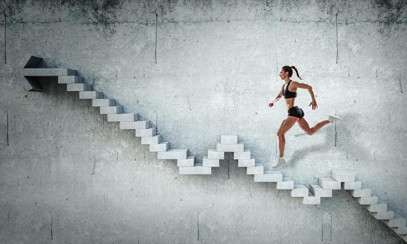 Νέο θηλυκό αθλητών που αναρριχείται στα σκαλοπάτια πετρών που επεξηγούν την ανάπτυξη σταδιοδρομίας και την έννοια επιτυχίας Μικτά στοκ φωτογραφία με δικαίωμα ελεύθερης χρήσης