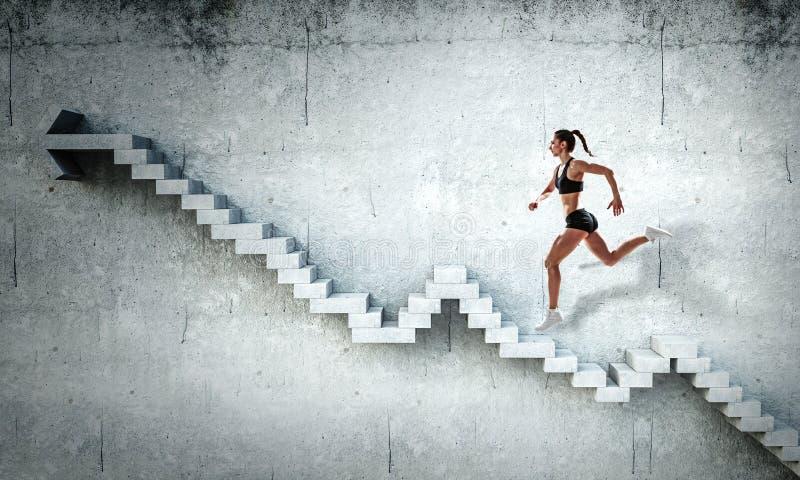 Νέο θηλυκό αθλητών που αναρριχείται στα σκαλοπάτια πετρών που επεξηγούν την ανάπτυξη σταδιοδρομίας και την έννοια επιτυχίας r στοκ εικόνες