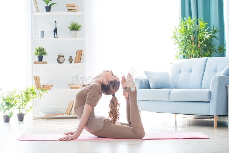 Νέο θηλυκό γυναικών ικανότητας όμορφο που κάνει την εκτροπή και τη γιόγκα αθλητικής άσκησης workout στο χαλί το πρωί Υγιής τρόπος στοκ φωτογραφία με δικαίωμα ελεύθερης χρήσης