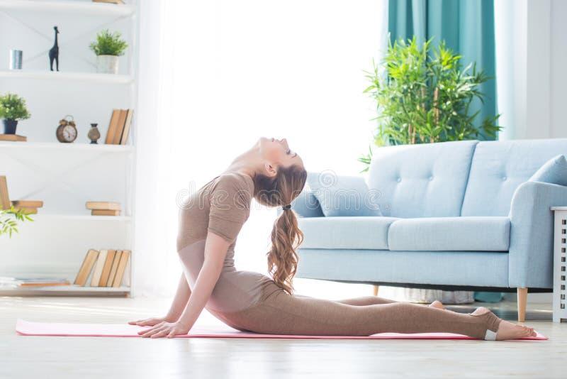 Νέο θηλυκό γυναικών ικανότητας όμορφο που κάνει την εκτροπή και τη γιόγκα αθλητικής άσκησης workout στο χαλί το πρωί Υγιής τρόπος στοκ φωτογραφίες με δικαίωμα ελεύθερης χρήσης