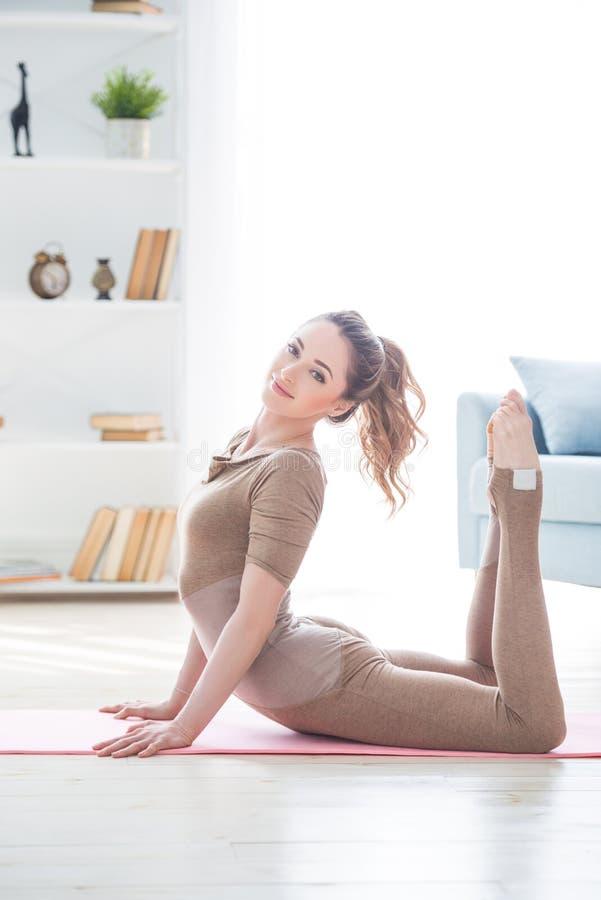 Νέο θηλυκό γυναικών ικανότητας όμορφο που κάνει την εκτροπή και τη γιόγκα αθλητικής άσκησης workout στο χαλί το πρωί Υγιής τρόπος στοκ εικόνες