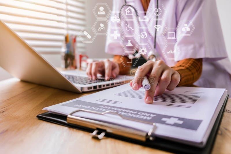 Νέο θηλυκό σε ομοιόμορφο του γιατρού χρησιμοποιώντας το ψηφιακό lap-top τεχνολογίας για τη συσκευή παραγωγής και γράφοντας μια υπ στοκ φωτογραφία