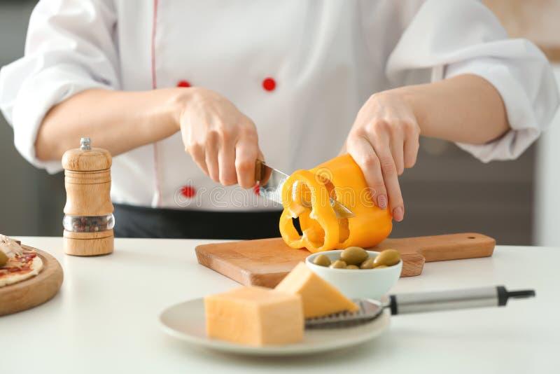 Νέο θηλυκό τέμνον πιπέρι αρχιμαγείρων στην κουζίνα, κινηματογράφηση σε πρώτο πλάνο στοκ εικόνα