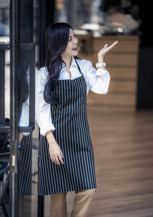Νέο θηλυκό barista που χαμογελά στεμένος στην πόρτα στοκ φωτογραφία με δικαίωμα ελεύθερης χρήσης