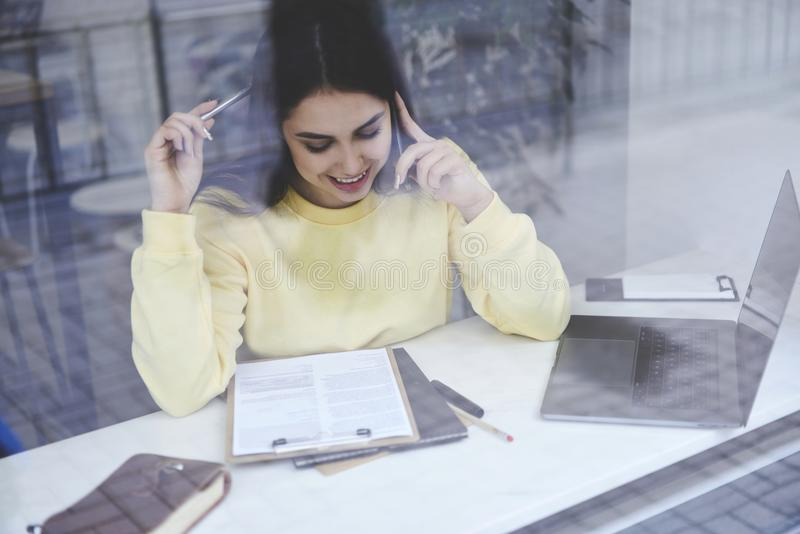 Νέο θηλυκό freelancer που μιλά στο κινητό τηλέφωνο στοκ φωτογραφία με δικαίωμα ελεύθερης χρήσης