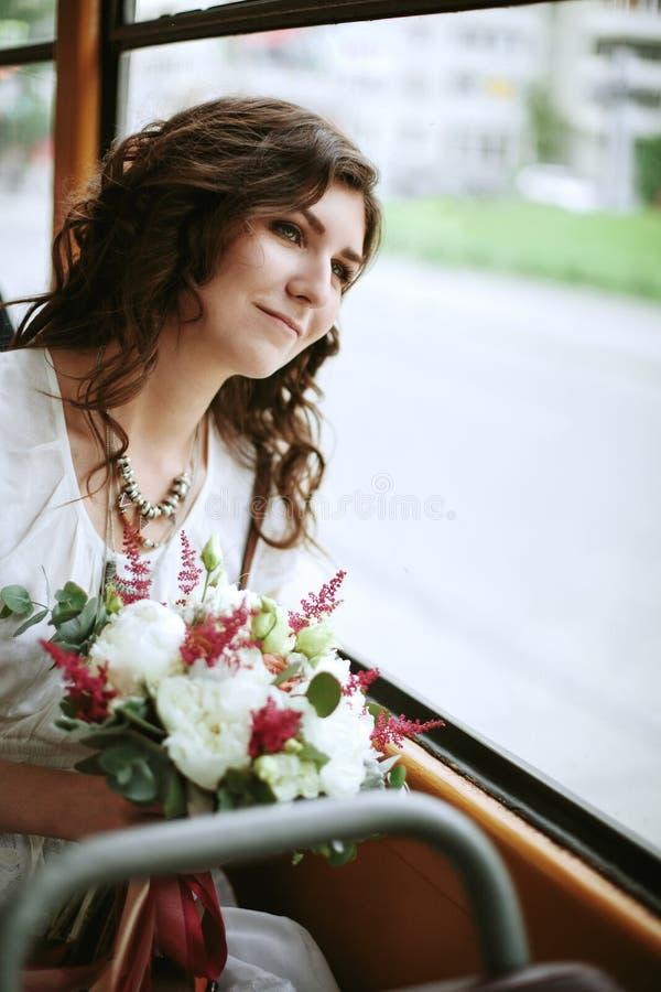 Νέο θηλυκό με τα λουλούδια που κάθεται κοντά στο παράθυρο στοκ εικόνες με δικαίωμα ελεύθερης χρήσης